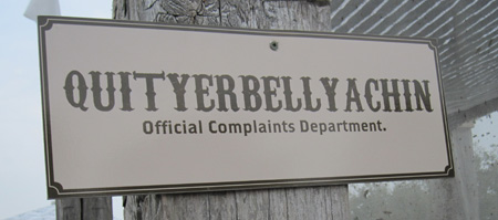 Sign on tent reads 'Official Complaints Department: QUITYERBELLYACHIN'